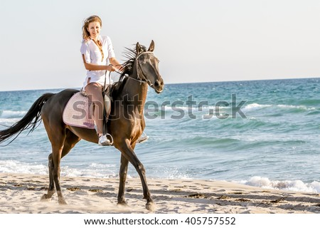Beautiful woman on a horse. Horseback rider, woman riding horse, sea background - stock photo