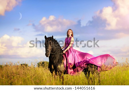 Beautiful woman on a horse with long pink dress