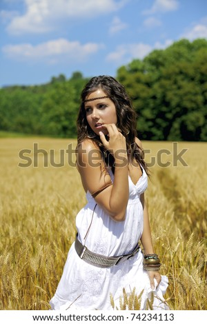 Beautiful woman on a wheat field during a hot summer afternoon. She dresses in white. Color photography full of warm and friendly colors. - stock photo