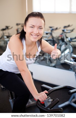 beautiful woman on an exercise bike at the gym