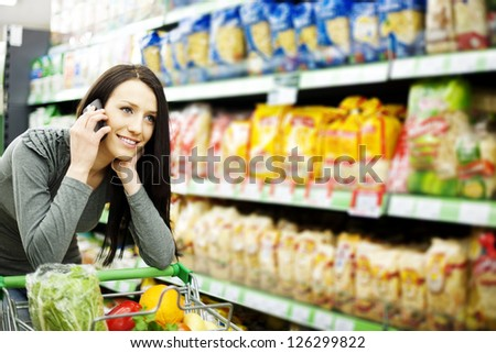 Beautiful woman on mobile phone at supermarket - stock photo