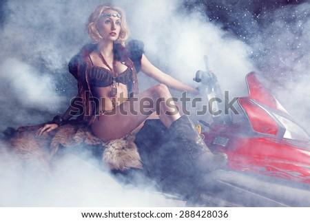 Beautiful woman on snowmobile  - stock photo