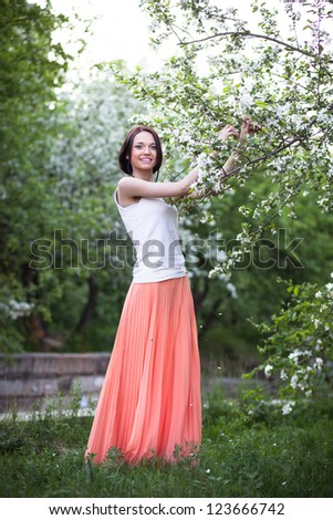 Beautiful woman on the background of a blossoming apple tree - stock photo