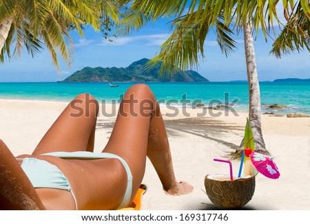 Beautiful woman on the beach enjoying a coconut cocktail in Thailand. - stock photo