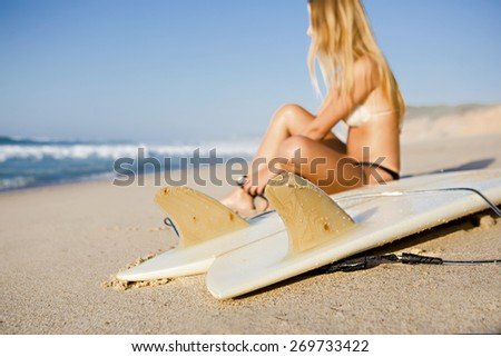 Beautiful woman on the beach getting ready for surf - stock photo