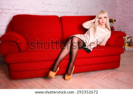 Beautiful woman on the bed,red sofa - stock photo