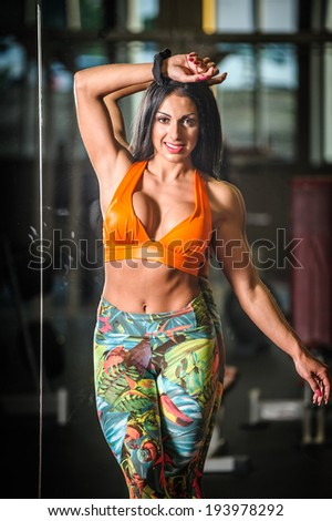 beautiful woman on the gym posing and standing - stock photo