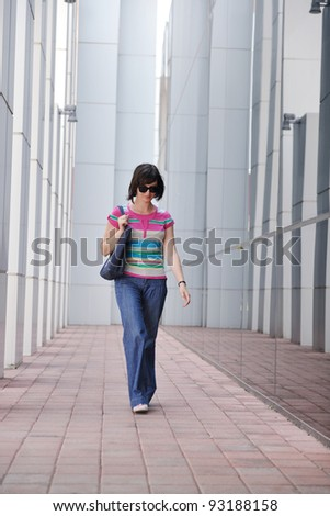 Beautiful woman  outdoor modern city urban street scene with abstract  glass reflections - stock photo