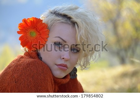 Beautiful woman outdoor portrait on a sunny day and red flowers
