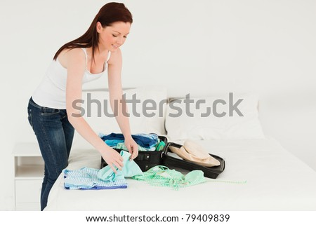 Beautiful woman packing her suitcase in her bedroom - stock photo