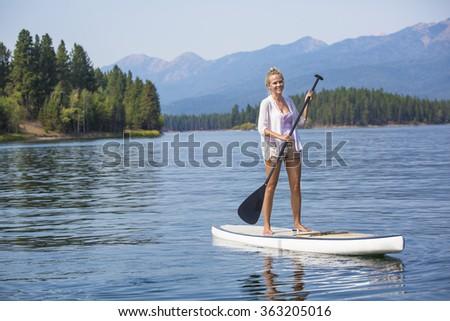 Beautiful woman paddle boarding on scenic mountain lake - stock photo