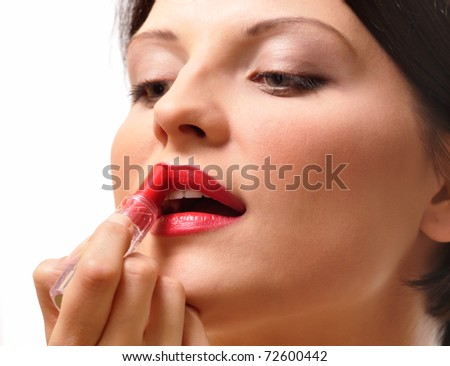 Beautiful woman painting her lips with lipstick - stock photo