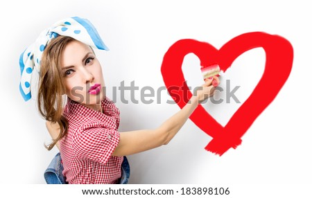 Beautiful woman paints the wall and drawing heart symbol - stock photo