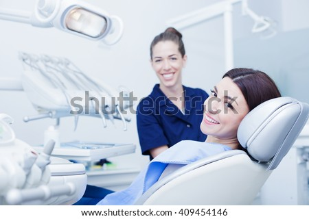 Beautiful woman patient having dental treatment at dentist's office. Woman visiting her dentist - stock photo