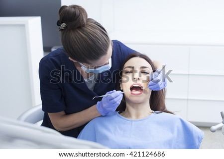 Beautiful woman patient having dental treatment at dentist's office. Women dentist