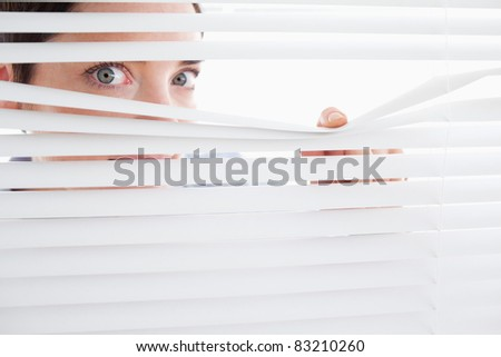 Beautiful Woman peeking out of a window in an office - stock photo