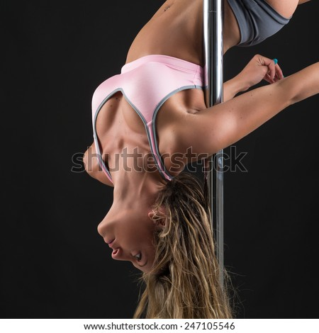 Beautiful woman performing pole dance upside down. Studio shot on black background. - stock photo