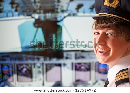 Beautiful woman pilot wearing uniform with epaulets, hat with golden wings sitting inside airliner with visible cockpit during flight. - stock photo