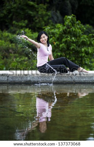 Beautiful woman play with water in park by the lake