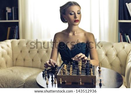 beautiful woman playing chess - stock photo