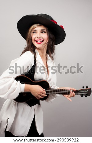 beautiful woman playing guitar with expression in zorro hat - stock photo