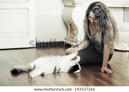 Beautiful woman playing with a cat on the floor - stock photo