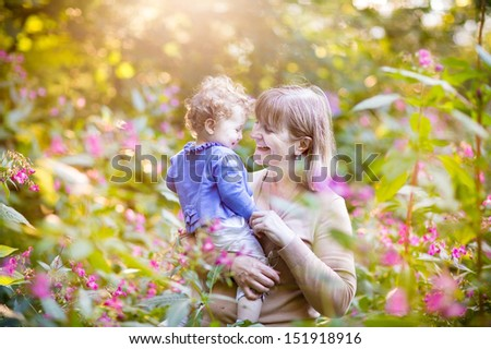 Beautiful woman playing with a happy baby girl in a garden at sunset among pink and red wild flowers - stock photo