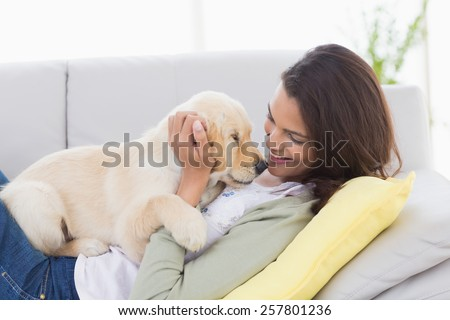 Beautiful woman playing with puppy while lying on sofa at home - stock photo