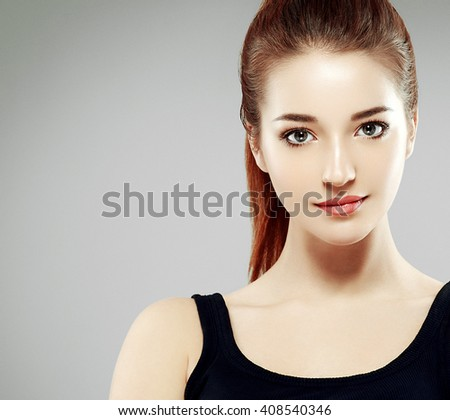 Beautiful woman portrait face studio isolated on gray - stock photo