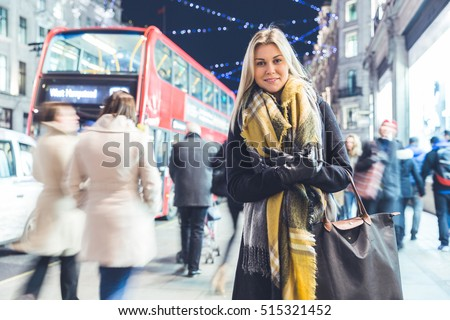 Beautiful woman portrait in London on Christmas time. Blonde woman, on her early twenties, wearing warm clothes and looking at camera. Christmas lights on background. Cold colours applied for the mood