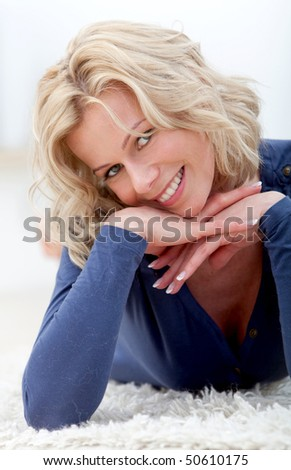 Beautiful woman portrait lying on the floor and smiling - stock photo