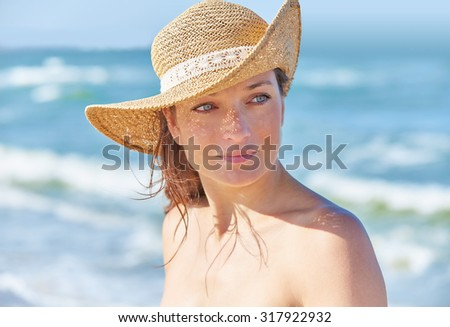 Beautiful woman portrait on the beach with hat - stock photo