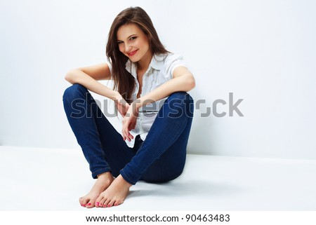 Beautiful woman portrait smiling and leaning against a wall - stock photo