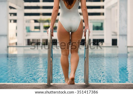 Beautiful woman portrait wearing swimsuit in swimming pool in Bangkok, Thailand. View from behind. Filtered image.  - stock photo