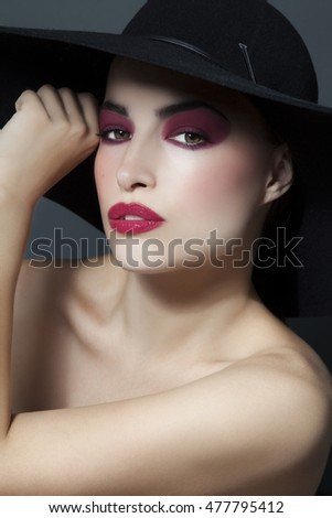 beautiful woman portrait with black hat and attractive red makeup