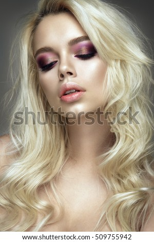 Beautiful woman portrait with blond hair on grey background.