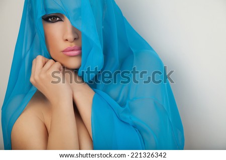 beautiful woman portrait with blue scarf over her head, studio white - stock photo