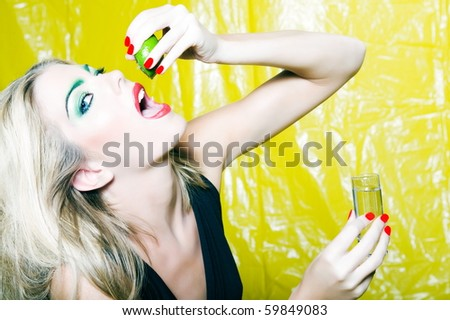 beautiful woman portrait with colorful make-up  and background drinking citrus juice