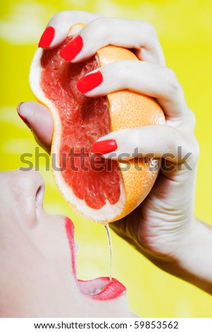 beautiful woman portrait with colorful make-up  and background drinking grapfruit juice - stock photo