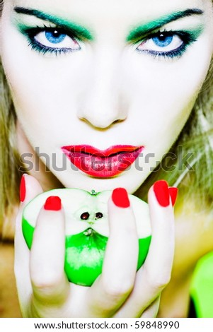 beautiful woman portrait with colorful make-up  and background holding apple - stock photo