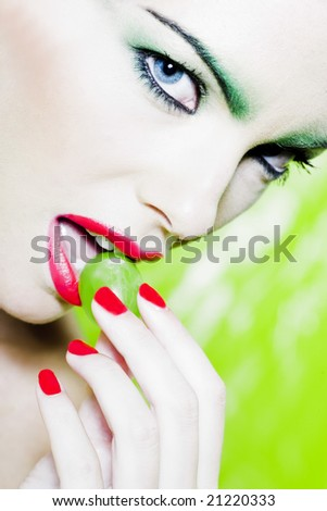 beautiful woman portrait with colorful make-up  and background holding grape - stock photo