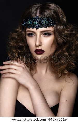 Beautiful woman portrait with green jewelry closeup isolated on black background. Fashion art Hairstyle and make up