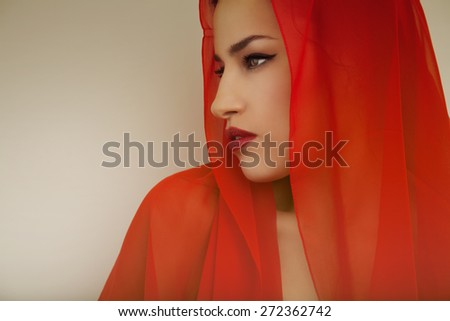 beautiful woman portrait with red lips and red veil over her head, studio shot - stock photo