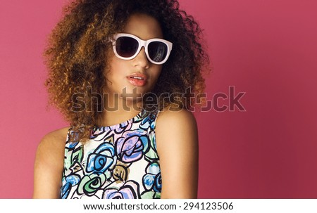 Beautiful woman posing in nice flower pattern dress and sunglasses on a pink background. Fashion photo with afro hairstyle. - stock photo