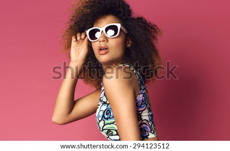 Beautiful woman posing in nice flower pattern dress and sunglasses on a pink background. Fashion photo with afro hairstyle.