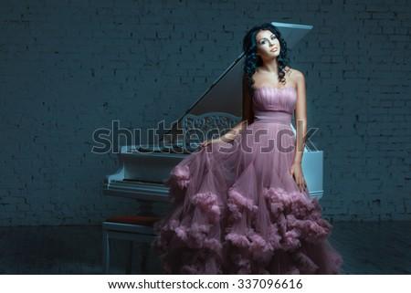 Beautiful woman posing next to a white piano. Her lush pink dress. - stock photo