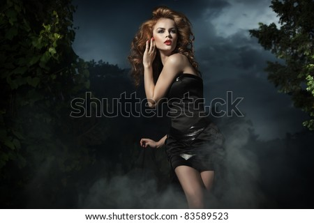 Beautiful woman posing on evening background - stock photo