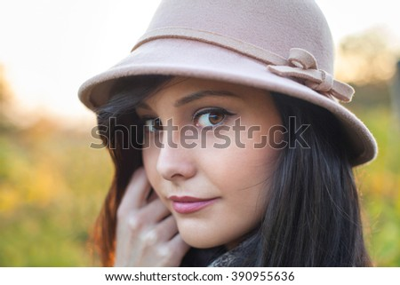 Beautiful woman posing with a hat looking at the camera. Autumn and spring portrait of beauty female model. Close up of caucasian young girl. Elegance lady in nature