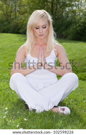 Beautiful woman practising yoga seated on green grass in the park with her hands folded together in meditation - stock photo