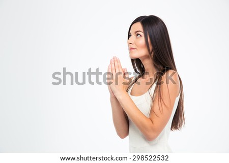 Beautiful woman praying isolated on a white background. Looking up - stock photo